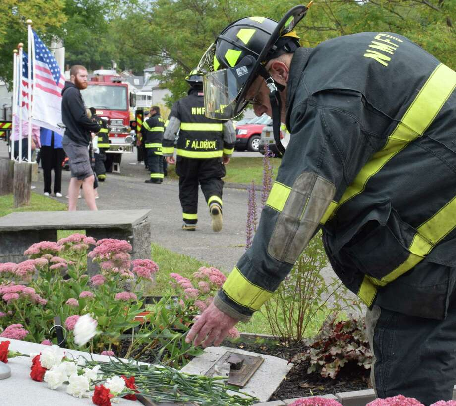 Bill Webster of Water Witch Hose Co. #2 places a flower at the base of New Milford's 9/11 memorial during Wednesday's commemoration ceremonies. Photo: Deborah Rose / Hearst Connecticut Media / The News-Times  / Spectrum