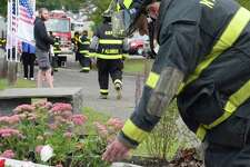 Bill Webster of Water Witch Hose Co. #2 places a flower at the base of New Milford's 9/11 memorial during Wednesday's commemoration ceremonies.