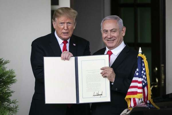 President Donald Trump and Benjamin Netanyahu, Israel's prime minister, hold up the signed proclamation recognizing Israel's sovereignty over the Golan Heights as Netanyahu departs the White House in Washington on March 25, 2019.