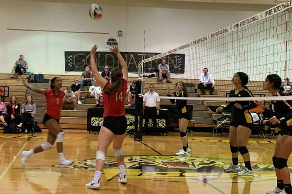 Memorial's Caroline Howell (14) sets a ball for Jada Gibson (2) during the Mustangs' sweep of Spring Woods, Sept. 17 at SWHS.