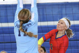 Roxana's Reagen Stahlhut (right) scores on a hit past the block of Jersey's Boston Talley in a match last month in Roxana. On Tuesday, Stahlhut had eight kills in the Shells' three-set victory over the rival Oilers in Wood River.
