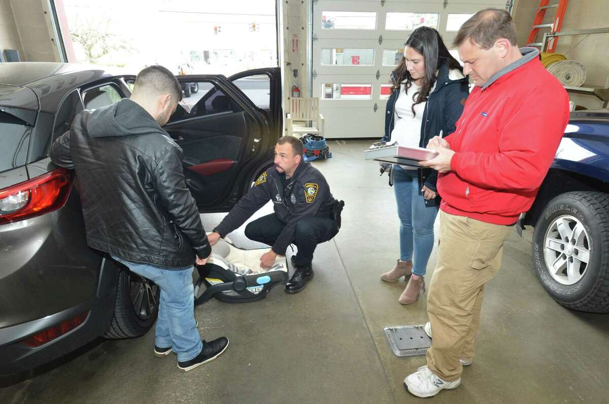 Alex Montoya watches as Norwalk Police Officer Christopher Wasilewski shows the correct tension for the straps on his infant carrier during a car seat check at Norwalk Fire Department station 4.
