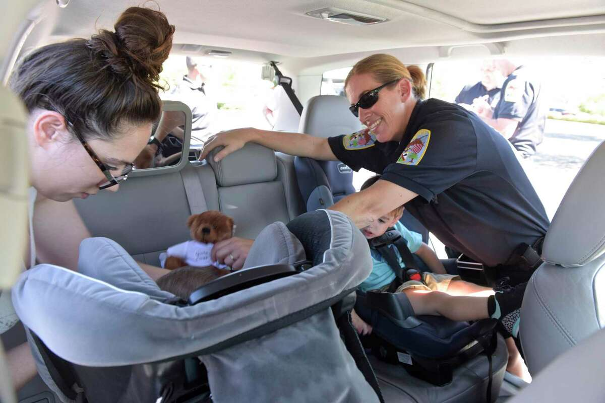 Danbury Police Office Melissa Morrill works with Amanda Capilipi, of Danbury, during a Car Seat Safety and Inspection Day hosted by the Danbury Police Department.