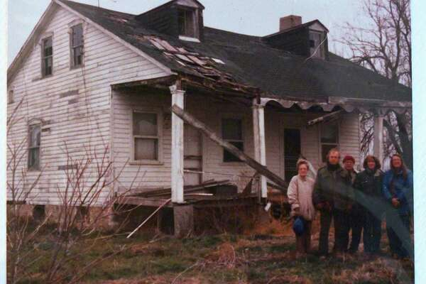 A photograph of a group of people belonging to the Schaefer and Sommerfeldt families standing before a dilapidated home is included in a color photo in a vintage photo album that Mike Rodriguez bought for $8 at a flea market in San Antonio. Other photos of the home in the album show it in pristine condition in the 1800s.