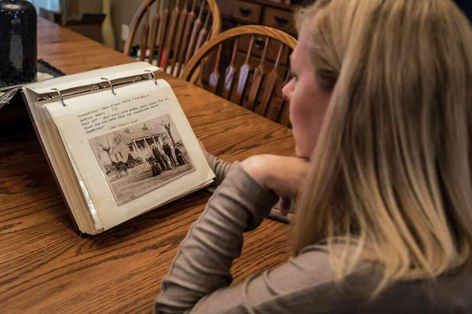 Julie Worthen of Prior Lake, Minn., sits at her dining room table on Sept. 11, looking through the old photo album mailed to her featuring many images of her family dating back to the 1800s. Photo: Nina Robinson /Contributor