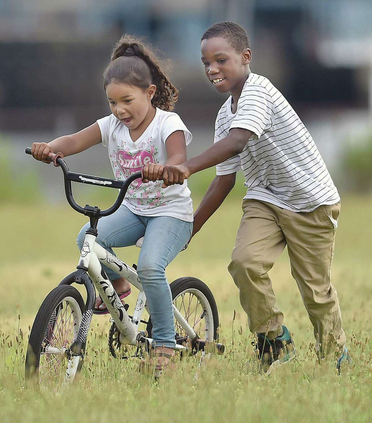 Naeem Jenkins, 10, teaches 5-year-old Kaylany Fargas how to ride a bike. We all need a little more kindness in our lives.