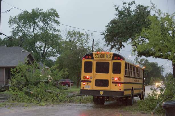 A school bus passes a fallen tree, Wednesday, Sept. 18, 2019, in Houston, as heavy rain from Tropical Depression Imelda falls. (Yi-Chin Lee/Houston Chronicle via AP)