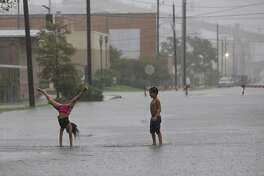 Jordan Sauceda, 8, right, watches his sister Jaslynn Sauceda, 7, making a cartwheel in the flood water outside their house on 30th Street on Wednesday, Sept. 18, 2019, in Galveston.