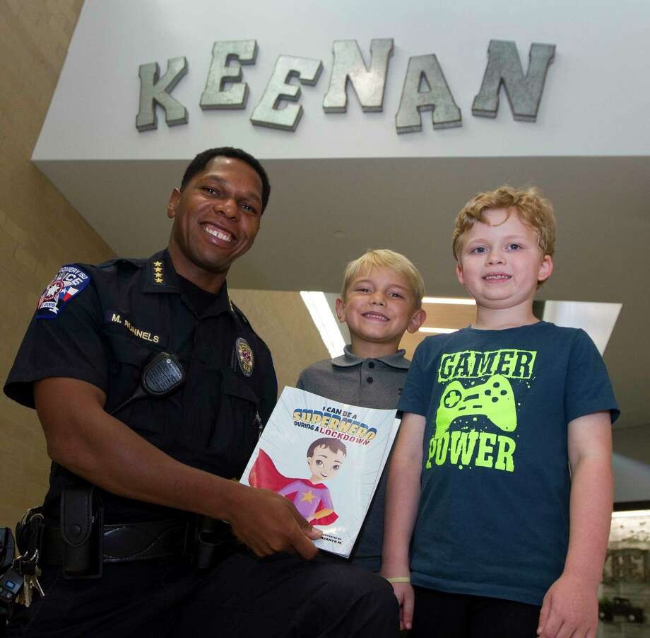 Montgomery ISD Police Chief Marlon Runnels, left, pose for a photo beside Keenan Elementary first grade students Lian Haverstock, center and Grayson Bishop recall hiding in a bathroom during a lockdown drill last year, Thursday, Sept. 12, 2019, in Montgomery. Bishop found Haverstock along in the hallway during the drill and the two decided to hide in the restroom for safety before being found by Runnels. Photo: Jason Fochtman, Houston Chronicle / Staff Photographer / Houston Chronicle