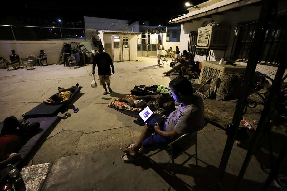 A Cuban man looks at a computer screen as others lay around at El Buen Pastor shelter in Cuidad Juarez, Mexico. Every evening, the 130 or so migrants are locked in at 5:30 p.m. Photo: Gregory Bull / Associated Press