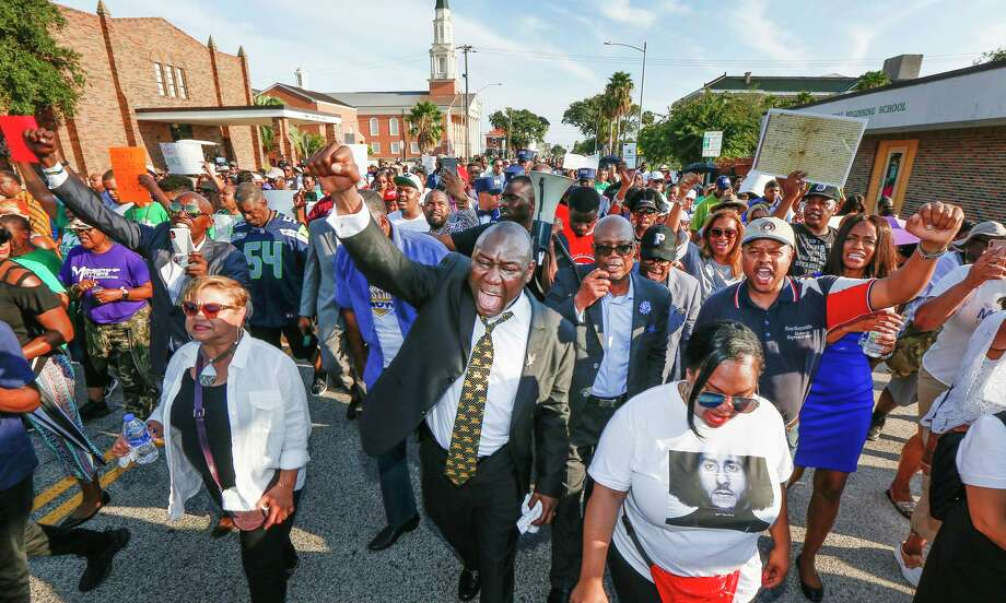 Attorney Benjamin Crump, center, and the Bishop James Dixon, behind, lead supporters of Donald Neely, the disabled man arrested and led by a rope by two mounted Galveston police officers on Aug. 3, on a march down 23rd Street, Sunday, Sept. 15, 2019, in Galveston, Texas. Marissa Barnett, City of Galveston, estimated about 250 gathered for the protest. (Steve Gonzales/Houston Chronicle via AP) Photo: Steve Gonzales, MBO / Associated Press / © 2019 Houston Chronicle