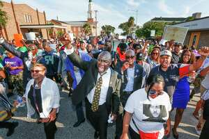 Attorney Benjamin Crump, center, and the Bishop James Dixon, behind, lead supporters of Donald Neely, the disabled man arrested and led by a rope by two mounted Galveston police officers on Aug. 3, on a march down 23rd Street, Sunday, Sept. 15, 2019, in Galveston, Texas. Marissa Barnett, City of Galveston, estimated about 250 gathered for the protest. (Steve Gonzales/Houston Chronicle via AP)