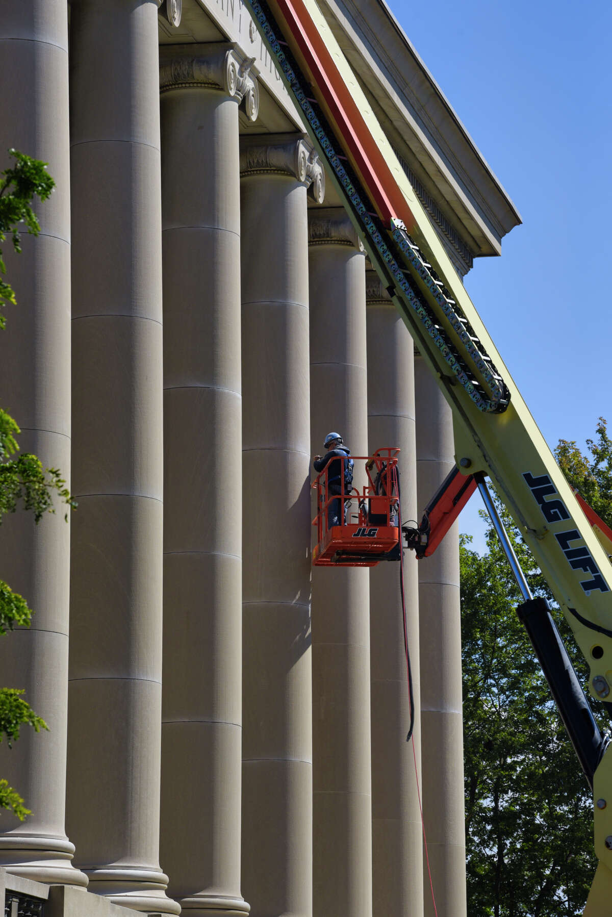 A man on a lift works on a column at the Schuyler Building at the University at Albany downtown campus on Wednesday, Sept. 18, 2019, in Albany, N.Y. Rehab work is being done on the building and when complete it will house the university's College of Engineering and Applied Sciences. (Paul Buckowski/Times Union)