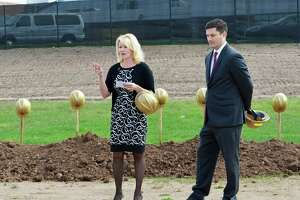 Common Council Deputy Majority Leader Mary Bartolotta, chairwoman of the middle school building committee, and Christopher Drake, chairman of the Board of Education, take part in the ceremonial groundbreaking for the new Woodrow Wilson Middle School in Middletown.