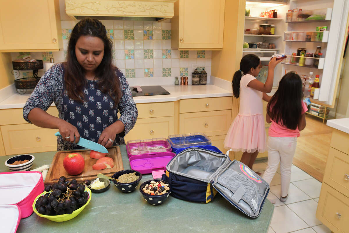 Aneesa Waheed and her daughters Zoya Shoaib, background left, 8, and Suha Shoaib, 7, work together to make the girl's school lunches on Monday, Sept. 16, 2019, at their home in Niskayuna, N.Y. (Paul Buckowski/Times Union)