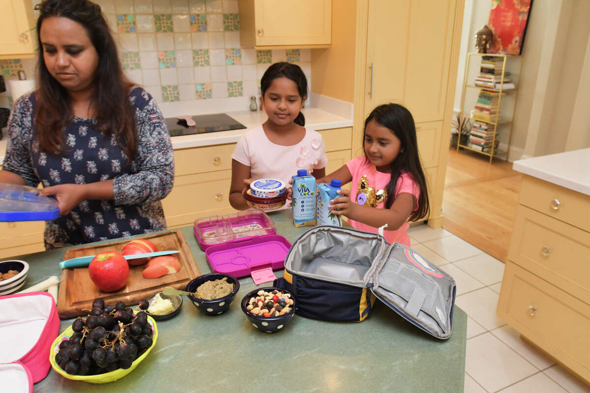 Aneesa Waheed and her daughters Zoya Shoaib, left, 8, and Suha Shoaib, 7, work together to make the girl's school lunches on Monday, Sept. 16, 2019, at their home in Niskayuna, N.Y. (Paul Buckowski/Times Union)