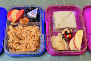 Aneesa Waheed's school lunch creations for her two daughters, seen here at her home on Monday, Sept. 16, 2019, Niskayuna, N.Y. The box on the left contains chicken curry and rice, almonds, grapes, cheese, and apple slices. The box on the right contains a peanut and mint chutney sandwich, hummus, trail mix, and apple slices.  (Paul Buckowski/Times Union)