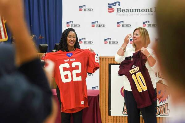 Beaumont United's principle Charisma Popillion on the left and West Brook's principle Diana Valdez hold the opposite school's jerseys during the West Brook vs. United football press conference before the Alumni Bowl game in BISD's board room Wednesday. Photo taken on Wednesday, 09/18/19. Ryan Welch/The Enterprise