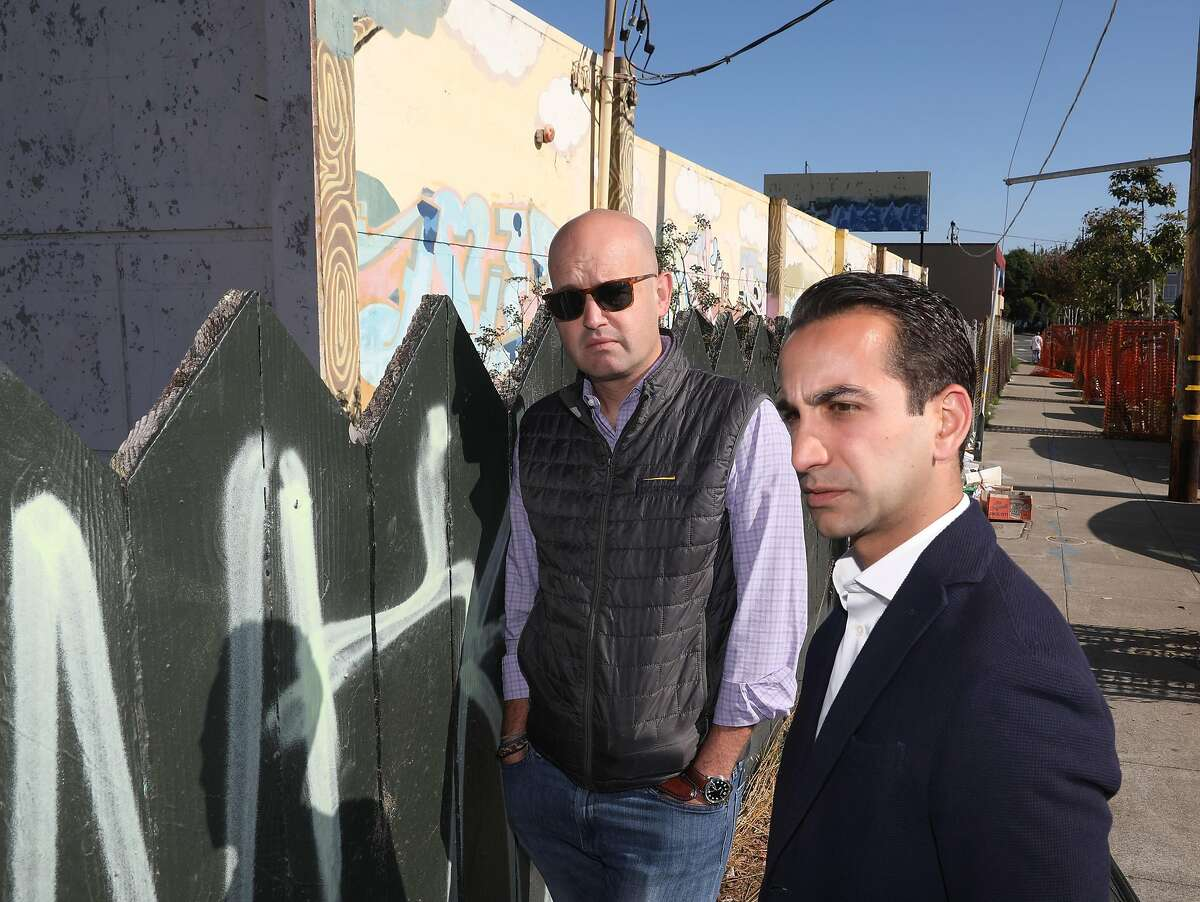 Developer Cyrus Sanandaji (right) from Presidio Bay Ventures and Lighthouse public affairs consultant Boe Hayward (left) talk about their housing project which includes the vacant school building at 65 Ocean Ave. (behind them) seen on Tuesday, Sept. 17, 2019 in San Francisco, Calif.