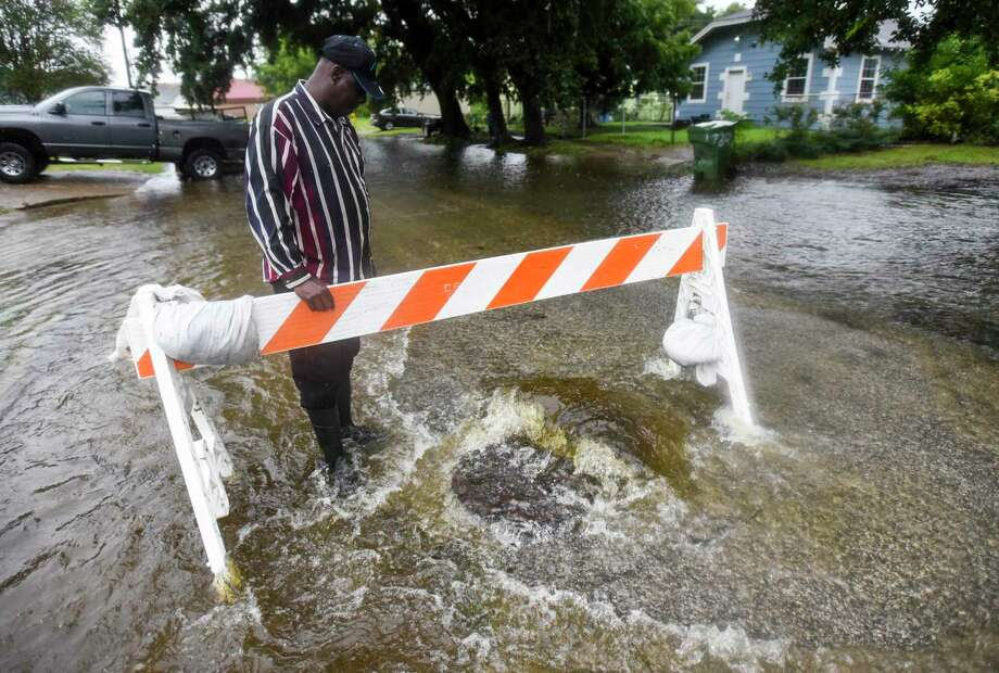 Eddie Davis, whole lives on the block, inspects a manhole as water gushes out of it on 11th Ave in between 8th Street and 7th Street in Port Arthur Wednesday afternoon. Photo taken on Wednesday, 09/18/19. Ryan Welch/The Enterprise Photo: Ryan Welch, Beaumont Enterprise / The Enterprise / © 2019 Beaumont Enterprise