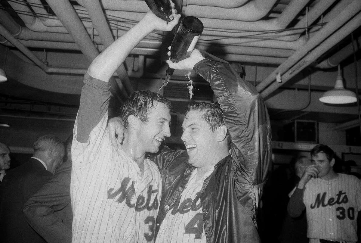(Original Caption) 9/24/1969-New York, NY- Up until 9:07 pm,the greatest achievement of man may well have been the landing on the moon,but that's all changed now,at least for a great many baseball fans. At that time the New York Mets-the sport's eight-year-old put-on-won the National League's Eastern Division title.After the team's 6-0 clincher over the St.Louis Cardinals,Mets' mound mainstays Jerry Koosman(l, 16-9)and Tom Seaver(24-7)try to drown themselves in champagne. They watched the game from the bench as....