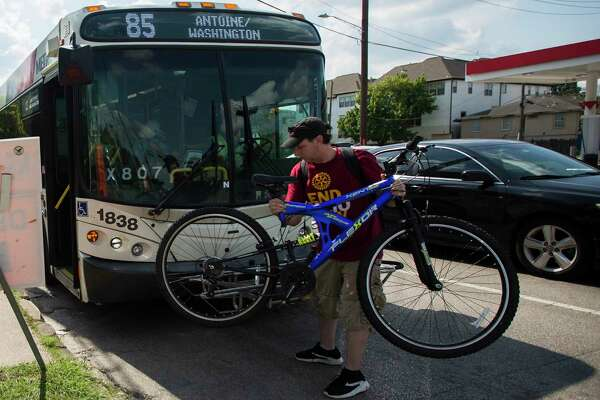 A rider removes his bicycle from the front of a Metropolitan Transit Authority Route 85 bus at the intersection of Washington and Studemont in Houston on June 10, 2019.