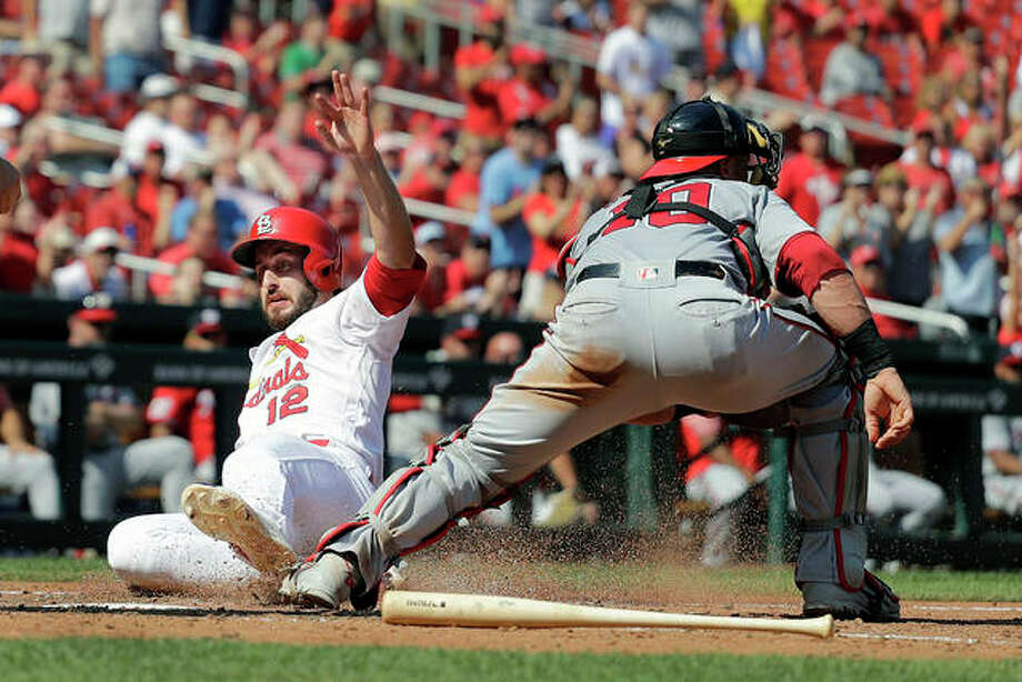The Cardinals' Paul DeJong (12) scores past Washington Nationals catcher Yan Gomes in the seventh inning Wednesday's game in St. Louis. Photo: AP Photo