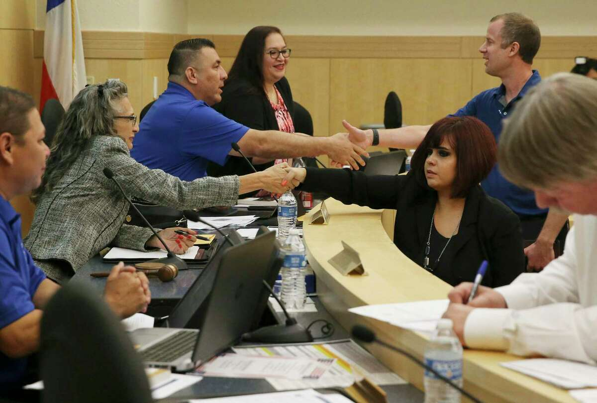Stacey Estrada (right) shakes hands with South San Board President Connie Prado and Kevin Rasco (right) shakes hands with Trustee Gilbert F. Rodriguez as Estrada and Roscoe were voted in as trustees during the South San school board meeting on Wednesday, Sept. 18, 2019. Estrada and Roscoe replaced two of the three trustees who abruptly resigned recently. (Kin Man Hui/San Antonio Express-News)