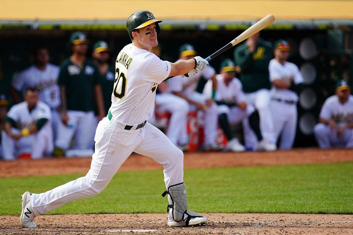 OAKLAND, CALIFORNIA - SEPTEMBER 18: Mark Canha #20 of the Oakland Athletics hits a walk off double during the twelfth inning against the Kansas City Royals at Ring Central Coliseum on September 18, 2019 in Oakland, California. (Photo by Daniel Shirey/Getty Images)