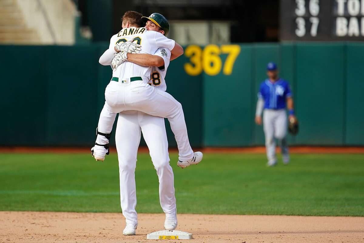OAKLAND, CALIFORNIA - SEPTEMBER 18: Mark Canha #20 of the Oakland Athletics celebrates a walk off double with Matt Olson #28 during the twelfth inning against the Kansas City Royals at Ring Central Coliseum on September 18, 2019 in Oakland, California. (Photo by Daniel Shirey/Getty Images)