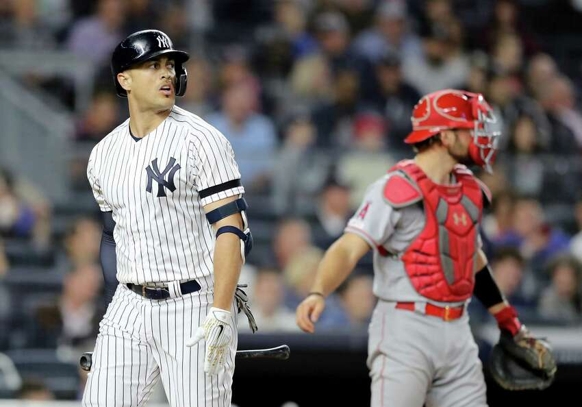 NEW YORK, NEW YORK - SEPTEMBER 18: Giancarlo Stanton #27 of the New York Yankees reacts after he struck out in the sixth inning as Kevan Smith #44 of the Los Angeles Angels looks on at Yankee Stadium on September 18, 2019 in the Bronx borough of New York City. (Photo by Elsa/Getty Images)