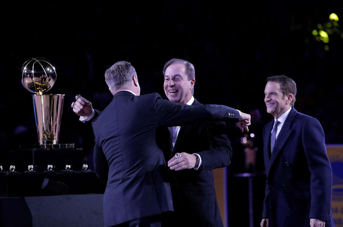 Rick Welts hugs Warriors owner Joe Lacob as owner Peter Guber watches after recieveing his champtionship ring before the Golden State Warriors played the Oklahoma City Thunder at Oracle Arena in Oakland, Calif., on Tuesday, October 16, 2018. The Warriors received their 2018 NBA Championship rings and saw their championship banner raised in the arena