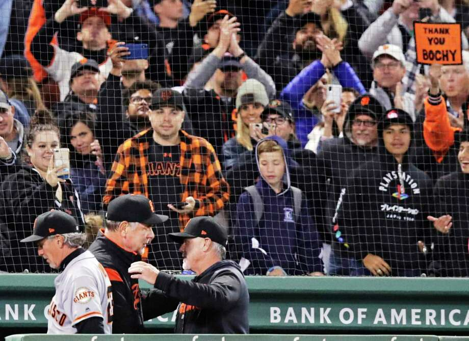 Fans watch as San Francisco Giants manager Bruce Bochy, center, is congratulated after the Giants defeated the Boston Red Sox 11-3 in a baseball game for his 2,000th career win, at Fenway Park in Boston, Wednesday, Sept. 18, 2019.  Photo: Charles Krupa / Associated Press / Copyright 2019 The Associated Press. All rights reserved.