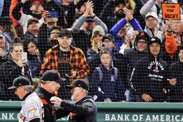 Fans watch as San Francisco Giants manager Bruce Bochy, center, is congratulated after the Giants defeated the Boston Red Sox 11-3 in a baseball game for his 2,000th career win, at Fenway Park in Boston, Wednesday, Sept. 18, 2019. (AP Photo/Charles Krupa)