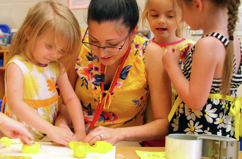 Skyah Arnold (from left), teacher Katie Williams, Kinley Kitner and Alessa McCollum work Wednesday on a poster of yellow items from around their classroom during Yellow Day activities at Early Years. Photo: Rosalind Essig | Journal-Courier