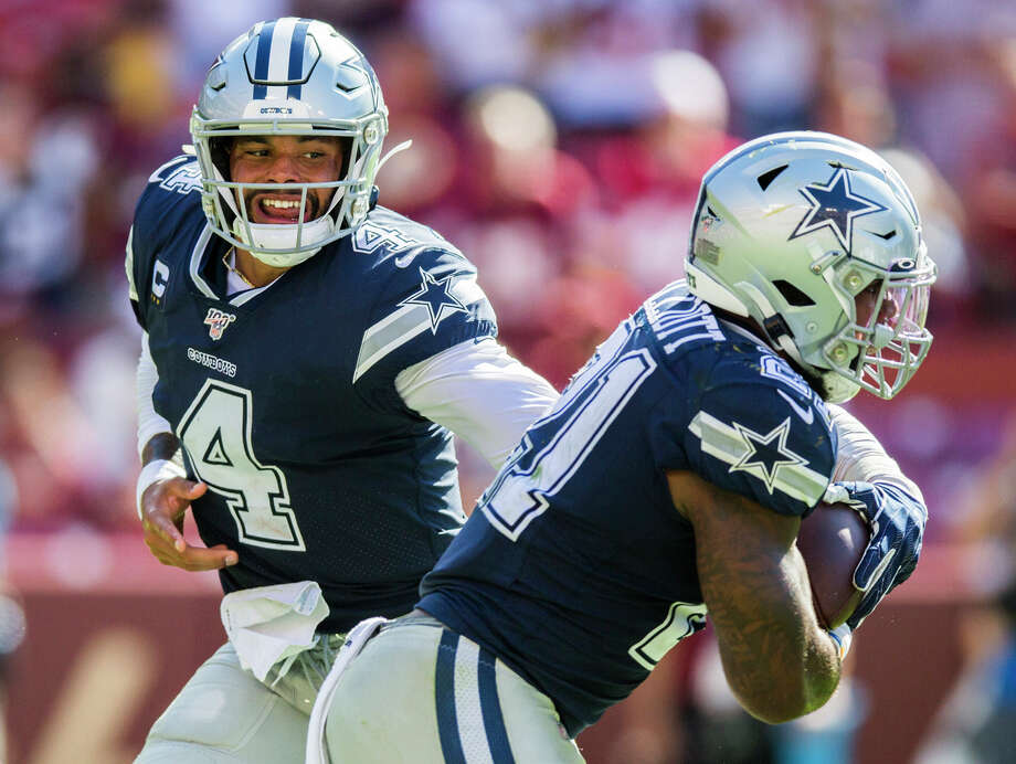 Dallas Cowboys quarterback Dak Prescott (4) hands off the ball to running back Ezekiel Elliott (21) during the fourth quarter against the Washington Redskins on Sunday, Sept. 15, 2019 at FedExField in Landover, Md. Photo: Ashley Landis, TNS / Dallas Morning News