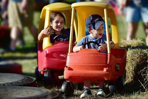 In this 2018 file photo, Sean Synnott, 3 and Michelle Imanov, 5, both of Orange get in a traffic jam riding cozy coupes at the Orange Country Fair Saturday, September 15, 2018, at the fairgrounds at 525 Orange Center Road in Orange.