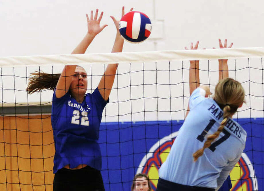 Marquette Catholic middle blocker Natalie Ellebracht (left) gets up for a block of an attack from Jersey's Boston Talley in an Aug. 27 match at the Roxana Tourney. Ellebracht had four kills and three aces in an Explorers win Wednesday night at Madison. Photo: Greg Shashack / The Telegraph