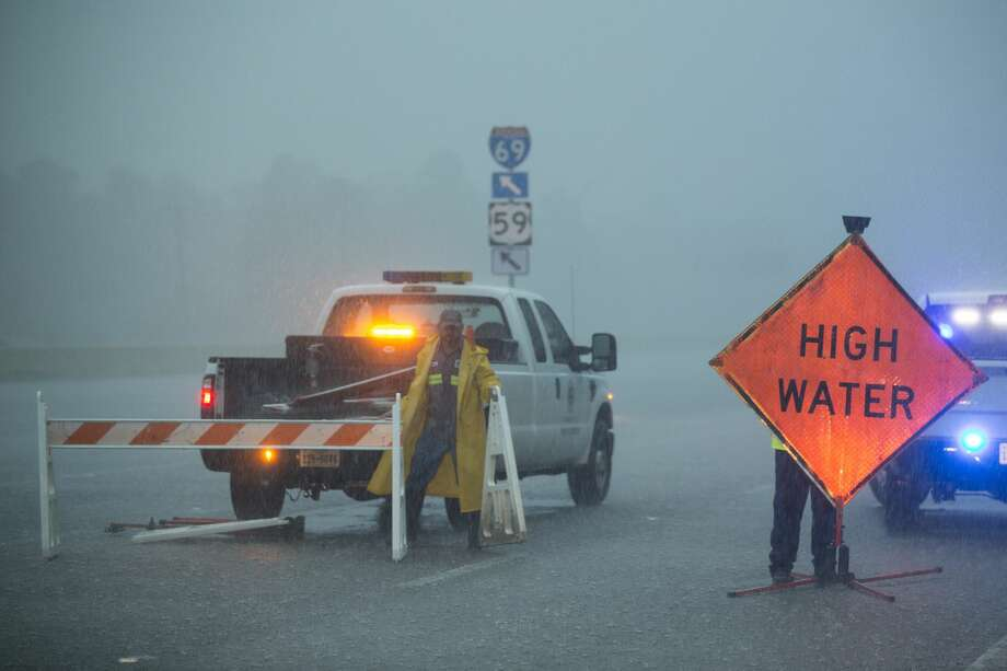 Crews block a flooded feeder road off U.S. 59 as rain from Tropical Depression Imelda inundates the area on Thursday, Sept. 19, 2019, near Spendora. Photo: Brett Coomer/Staff Photographer