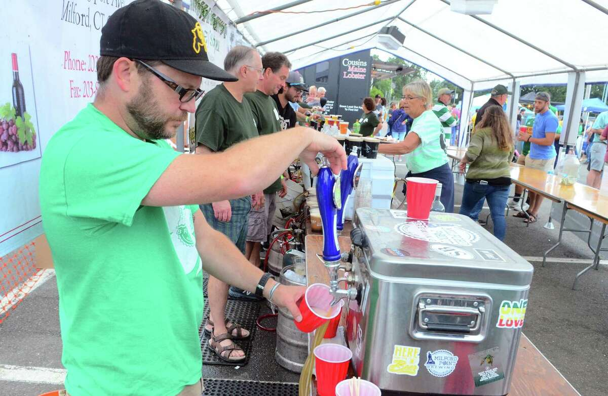 Chris Willett, with Milford Point Brewing, pours a beer during the annual Milford Irish Festival in Milford, Conn., on Friday Sept. 5, 2019.