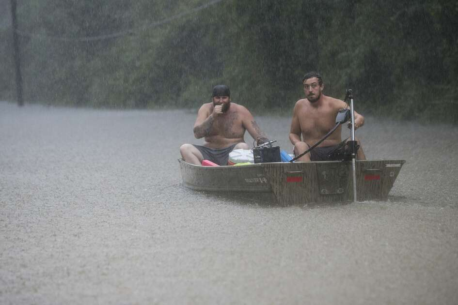 A pair of men get into a boat to float in to rescue a family trapped by floodwaters as rain from Tropical Depression Imelda inundates the area on Thursday, Sept. 19, 2019, near Patton Village.