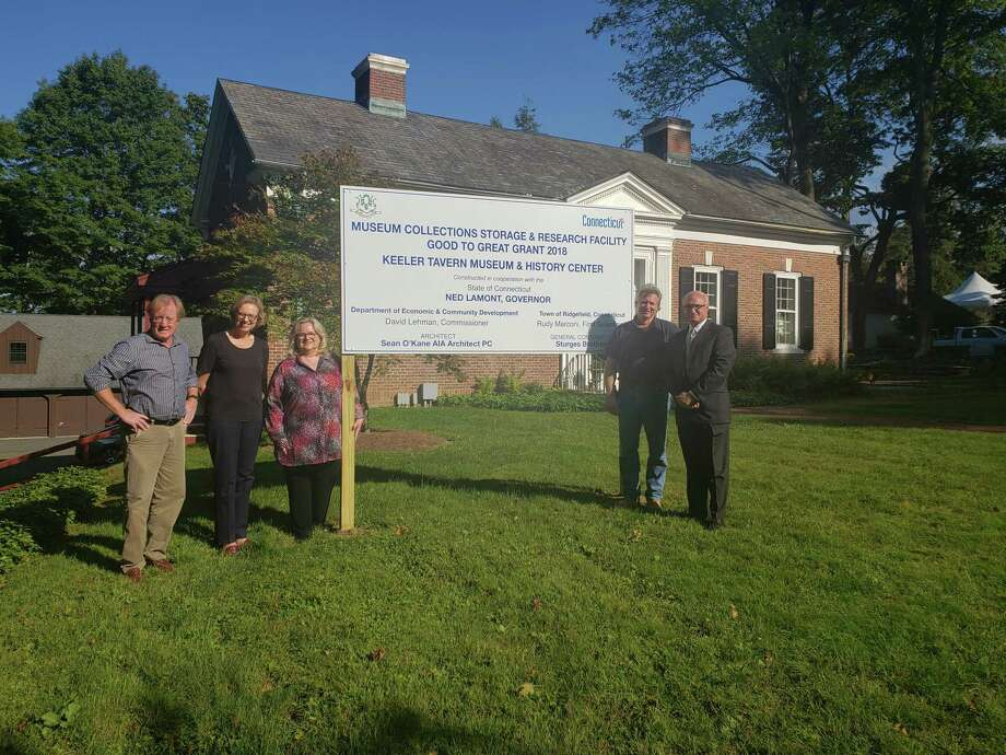 From left to right: Architect Sean O'Kane of Sean O'Kane AIA Architect PC; Keeler Tavern Museum & History Center Executive Director Hildegard Grob; KTM&HC Board President Rhonda Hill; Don Sturges of Sturges Brothers, Inc.; and First Selectman Rudy Marconi stand in front of the recently installed sign indicating that new construction on the site is partially funded by a 2018 Department of Economic and Community Development (DECD) Good to Great grant. The grant is substantially funding the creation of a state-of-the-art museum collections storage and research facility in the lower level of KTM&HC's new Visitor Center located at 152 Main Street in Ridgefield. Photo: Contributed Photo
