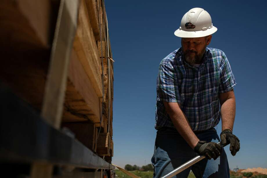 "Mike Wilkinson secures a stack of wooden pipeline skids onto his trailer at a site near Midland, Texas, May 21, 2019. Wilkinson was looking for a fresh start when he began working as a ""hot shot"" truck driver in the Permian Basin — the epicenter of the oil boom where the country's growing energy dominance has created tens of thousands of jobs in recent years. (Tamir Kalifa/The New York Times) Photo: TAMIR KALIFA/NYT"