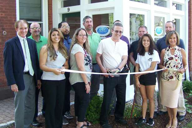 IT SOLUTIONS: From left Wallingford Mayor William Dickinson; Quinnipiac Chamber of Commerce board Chairman Frank DiCristina; Yessenia Stoff; Tim Escala; Office Manager Heather Abel; Chris Hyatt; founder and CEO Robert Mitchell; Ryan Kreger; Dave Dempster; Brigitte Mitchell; Clifton Waite; and Quinnipiac Chamber of Commerce Executive Director Dee Prior-Nesti celebrate the grand opening of ASG Information Technologies at 9 S. Cherry St. in Wallingford recently. ASG is a managed IT service provider for business clients both in and out of state. For information, visit www.asgct.com or call 203-440-4413.