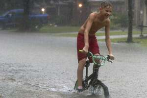A kid rides his bike near Kings Manor Drive as rain from Tropical Depression Imelda inundate the area, Thursday, Sept. 19, 2019, in Kingwood.