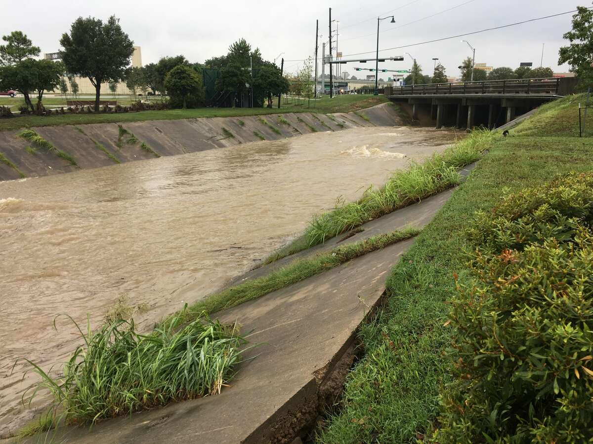 Alligator Creek runs swiftly next to McDonalds on Texas 105 in Conroe Thursday morning.