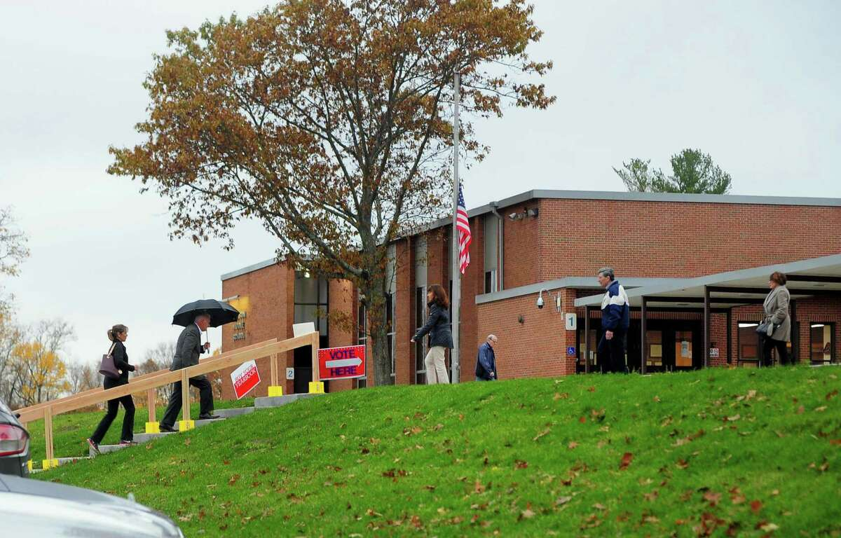 Voters enter and exit at the polling place at Hillcrest Middle School in Trumbull, Conn. on Tuesday Nov. 7, 2017.
