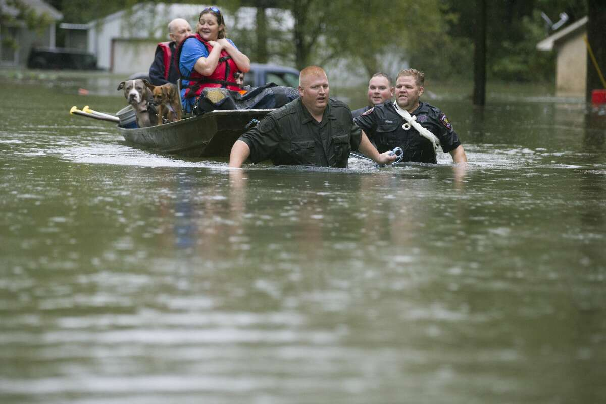 Splendora Police Lt. Troy Teller, left, Cpl. Jacob Rutherford and Mike Jones pull a boat carrying Anita McFadden and Fred Stewart from their flooded neighborhood inundated by rains from Tropical Depression Imelda on Thursday, Sept. 19, 2019, in Spendora.