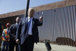 President Donald Trump talks with reporters as he tours a section of the southern border wall, Wednesday, Sept. 18, 2019, in Otay Mesa, Calif., as acting Homeland Secretary Kevin McAleenan listens, second from left. (AP Photo/Evan Vucci)
