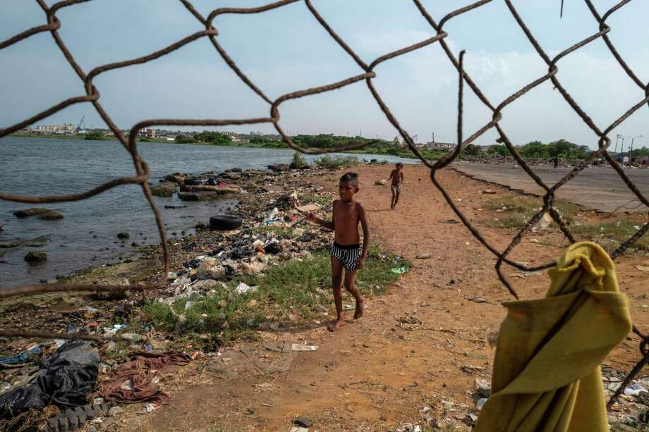Children play on a polluted beach along Lake Maracaibo. Photo: Washington Post Photo By Michael Robinson Chavez / The Washington Post